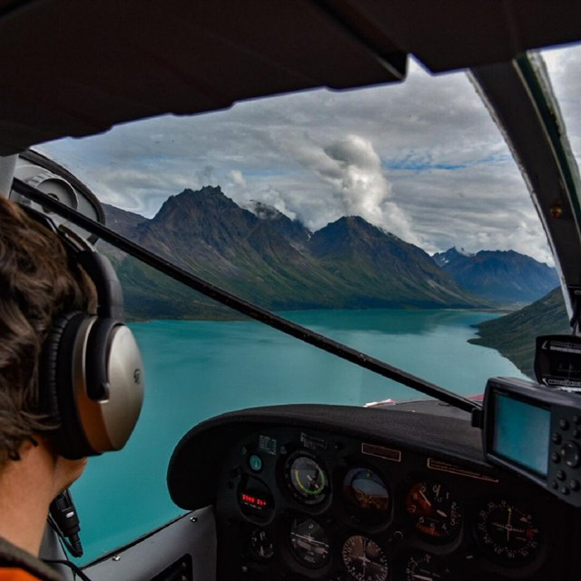 Float plane landing on a blue lake surrounded by steep mountains.