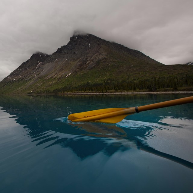 photo of a kayak paddle breaking the water's surface in a blue lake with a mountain in the distance.