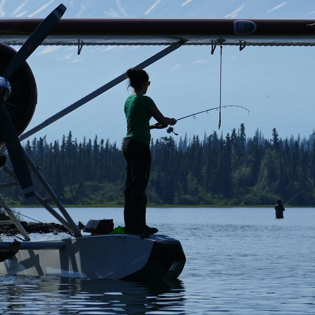 An angler fishes while standing on the float of a plane on a lake with mountains in the background