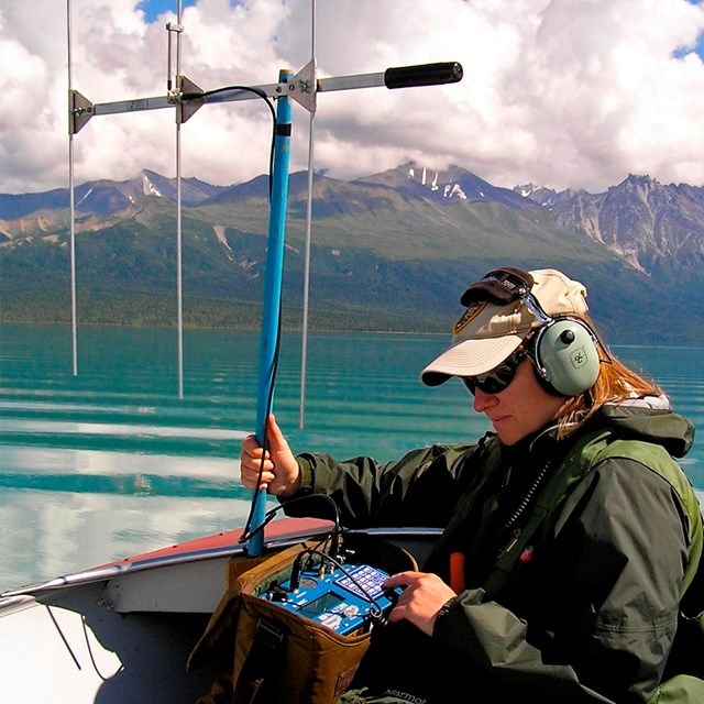 A woman holding a large antenna sits in a boat on a lake surrounded by colorful mountains.