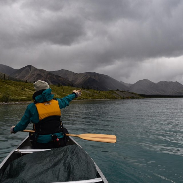 a woman in a canoe points towards a storm ahead