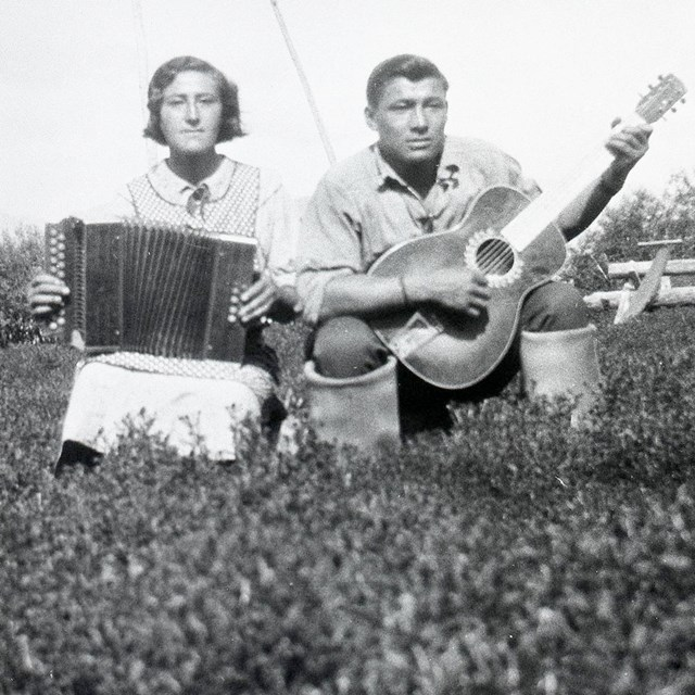 Historic image of woman playing accordion and man playing guitar.