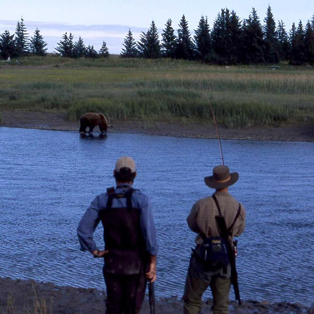 Two fishermen watch a brown bear on the opposite side of the river.