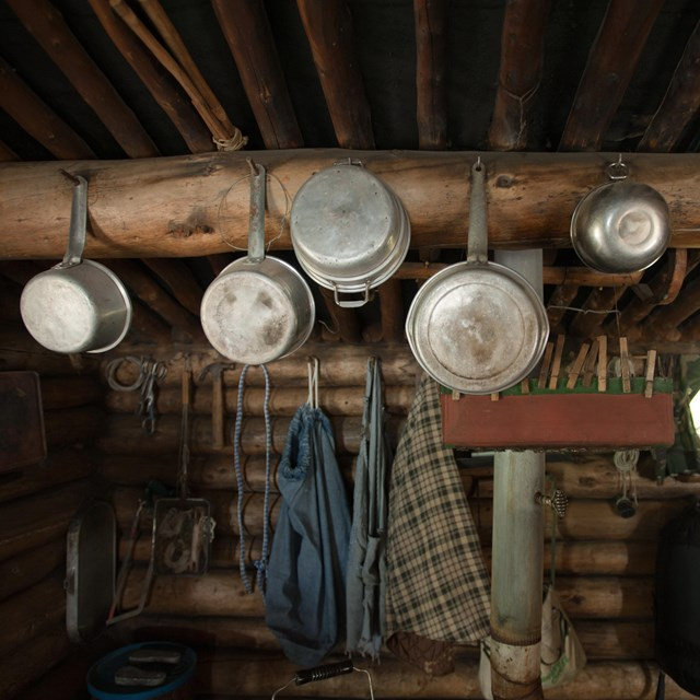 Pots and pans hang from a cabin wall