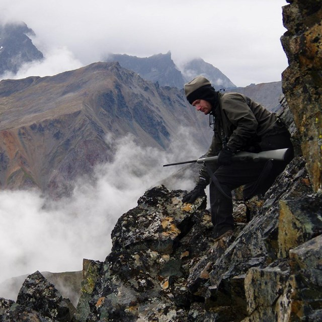 A man with a rifle sits on a steep, rocky slope