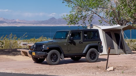 jeep parked near tent by lake