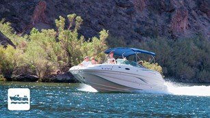 Motorboat riding on a lake in front of cliffs