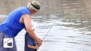 Man helping a child with a fishing pole