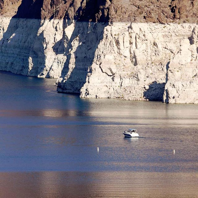 A boat cruises near the white band along the shore of Lake Mead NRA