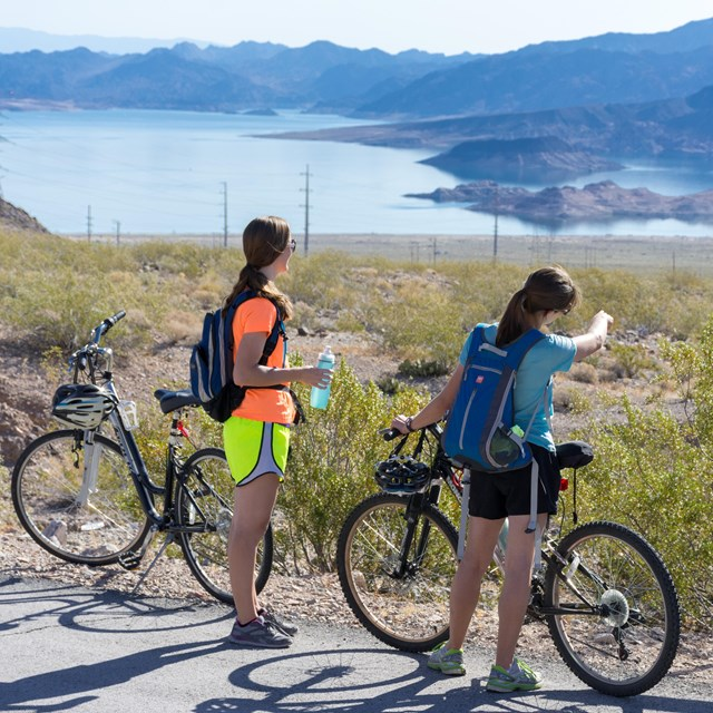 Three women looking over the lake. Two women are biker riders, one is a hiker.