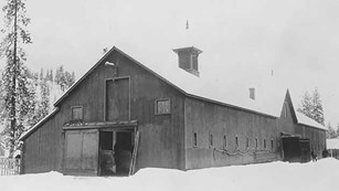 A historic black and white photo of the barn at Fort Spokane is shown.