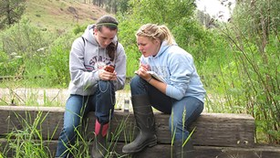 Two high school girls sit closely on old railroad ties while looking at a handheld GPS unit.