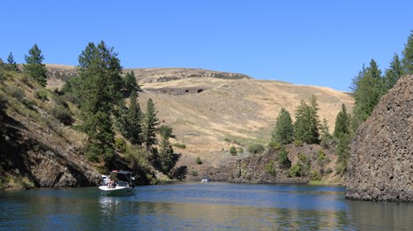 Two boats navigate their way down an arm of the lake with vertical basalt shores topped with pines.