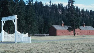 View of the white, wooden gate at Fort Spokane with the large mule barn behind.