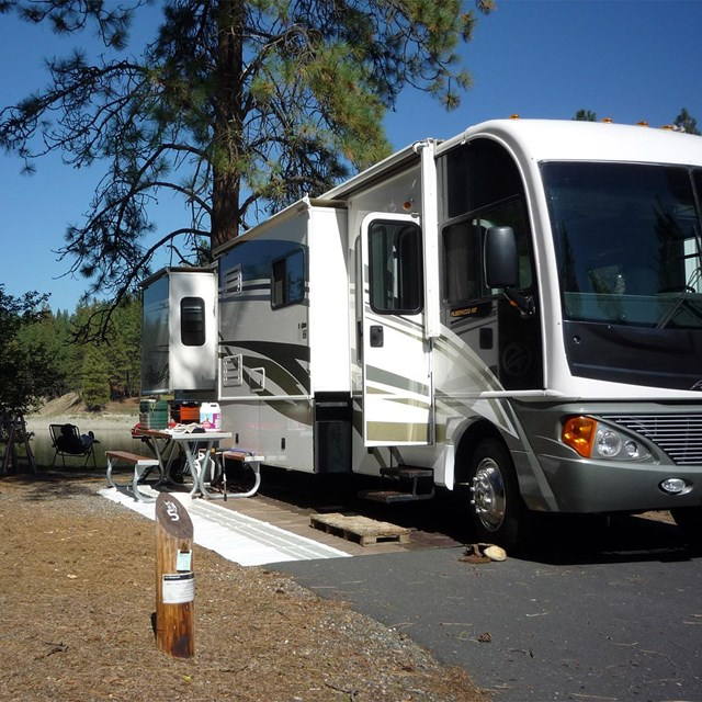 a white RV parked in a campsite with camping accessories spread across a picnic table
