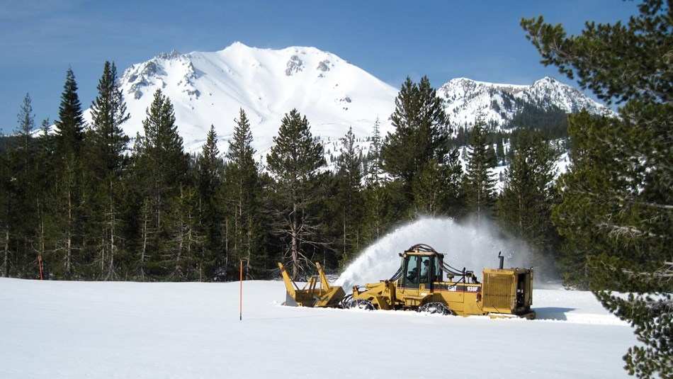 A yellow snowplow clears snow backed by a snow-covered mountain.