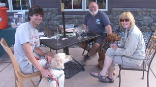 Visitors with leashed dogs at table