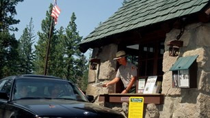 A man in a park ranger uniform hands a person in a vehicle from inside a small stone building