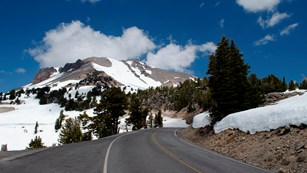 A highway curving toward a volcanic peak covered with large patches of snow