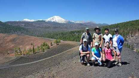 A group of hikers poses for a photo on the summit of a black ridge backed by a snow-capped volcano