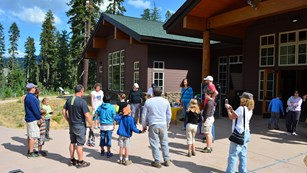 A group of people stand in a circle while conducting an activity outside of a wood building