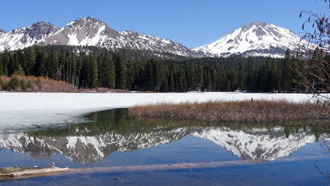 Two partially snow-covered volcanic peaks reflected in a partially frozen lake.