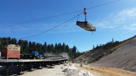 A load of lumber is transported by highline over a hydrothermal basin