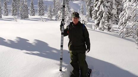 A woman in uniform stands on snowshoes next to a pole buried in snow