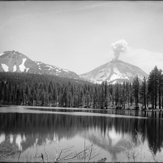 Black and white photo of a volcano with a small ash cloud fronted by a lake
