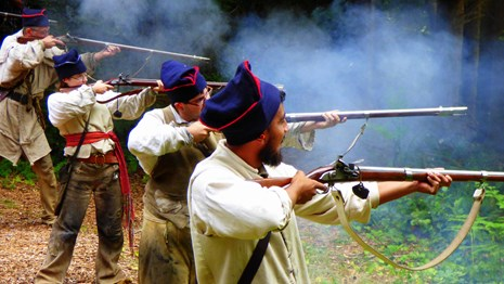Four rangers in a line shooting black powder muzzle loaders