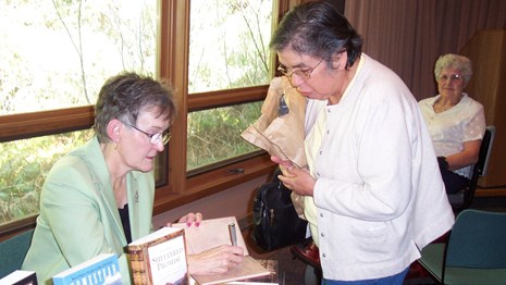 Guest speaker signing a book for an audience member.