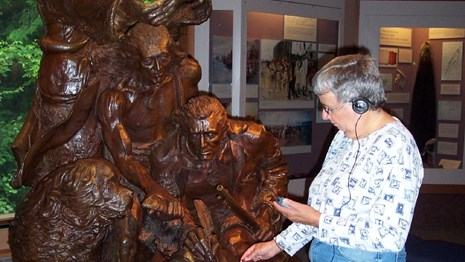 A woman holding a cell phone touching a large statue depicting Lewis and Clark listening to audio