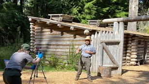 One ranger filming another ranger presenting in front of Fort Clatsop