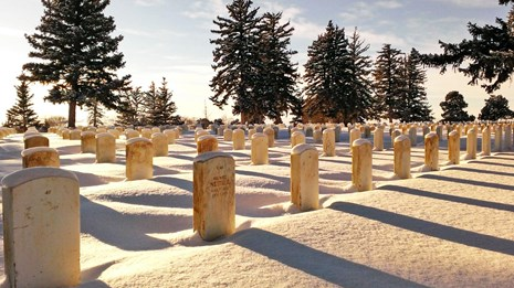 Snow blankets the ground around the headstones as the sun sets on the Custer National Cemetery.