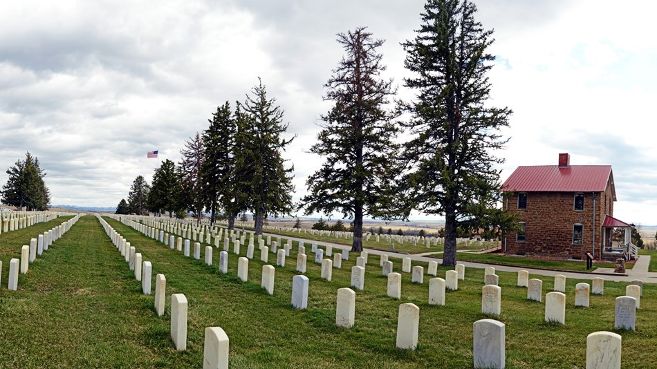 Custer National Cemetery markers with the Stonehouse to the right.
