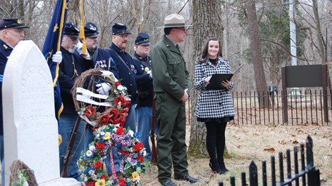 People in Civil War uniforms, park ranger and woman behind gravestone of Nancy Lincoln