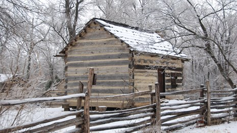 log cabin with split rail fence all covered with snow