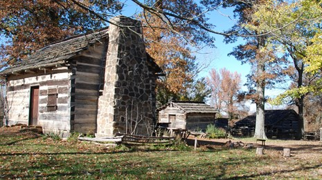 Log cabin and smokehouse surrounded by trees with brown leaves and blue sky