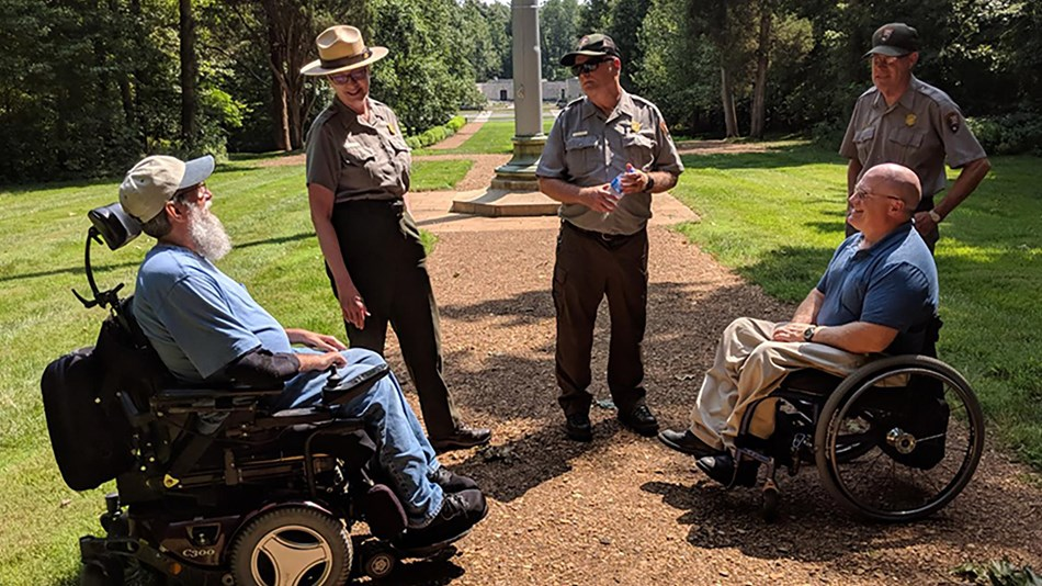 Three Park Rangers and two men in wheelchairs meet on park trail.