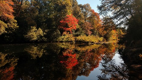Trees with red and orange fall colors are mirrored in Little River at Blue Hole.
