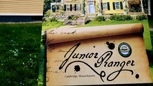 Junior Ranger book in front of a yellow house with green shutters and white trim.