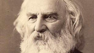 Bust-length portrait of Henry Longfellow with white hair and beard