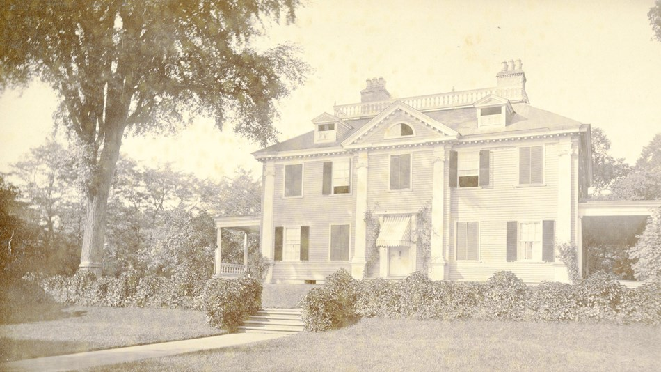 Black and white image of front of mansion with lawn in foreground