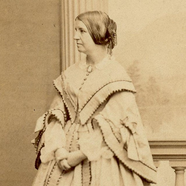 Full-length photograph of woman standing in floor-length dress