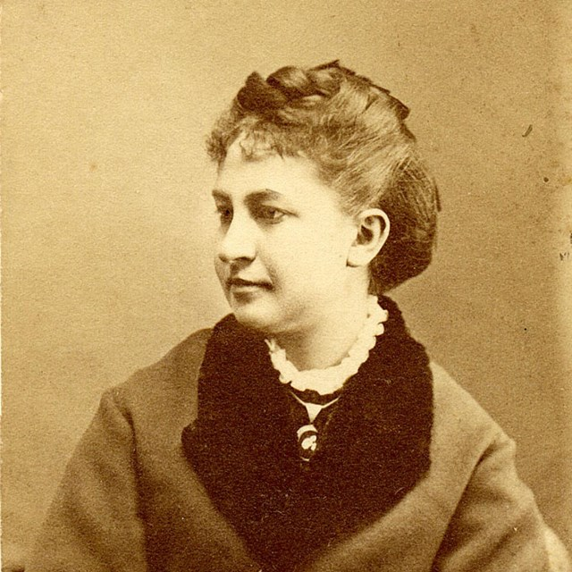 Portrait of young woman in coat with dark collar