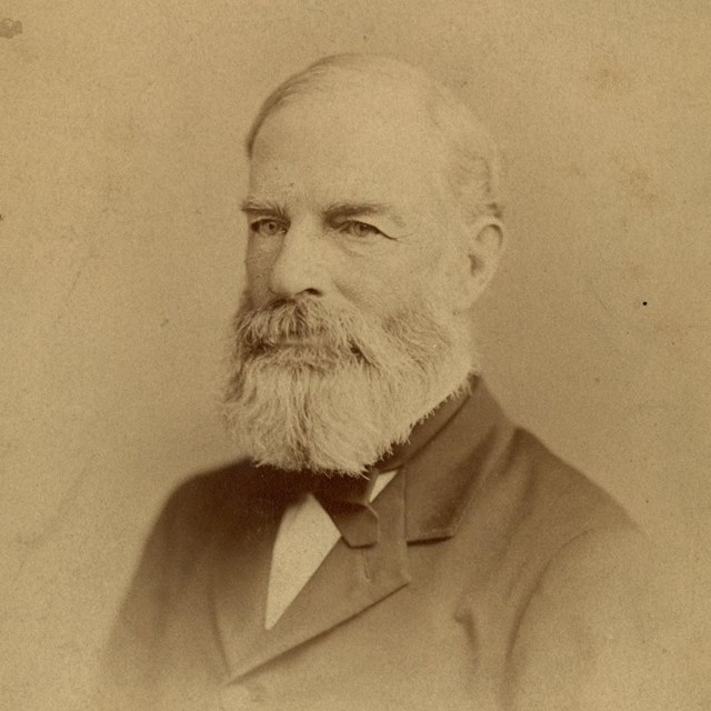 Bust-length portrait of man in suit with a beard
