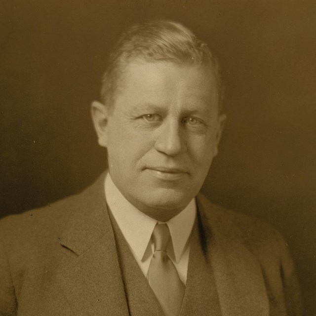 Studio portrait of man in three-piece suit and tie.