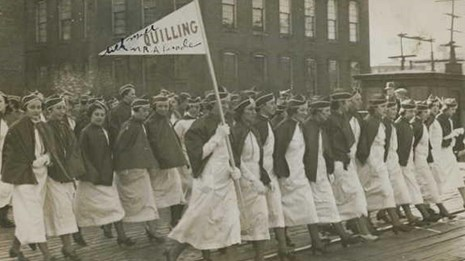 Women dressed in white marching in a parade holding flags