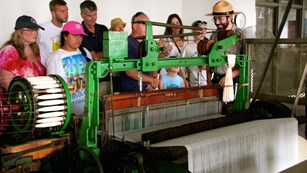 A park ranger explains an old metal weaving machine to a group of visitors of various ages.