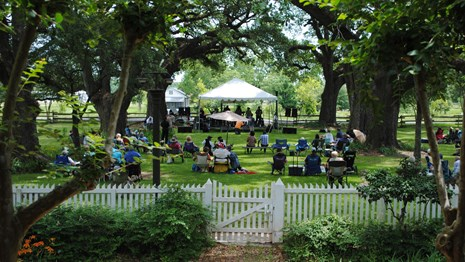 Visitors enjoy music at the annual Cane River Music Festival under the shade of the oak alley